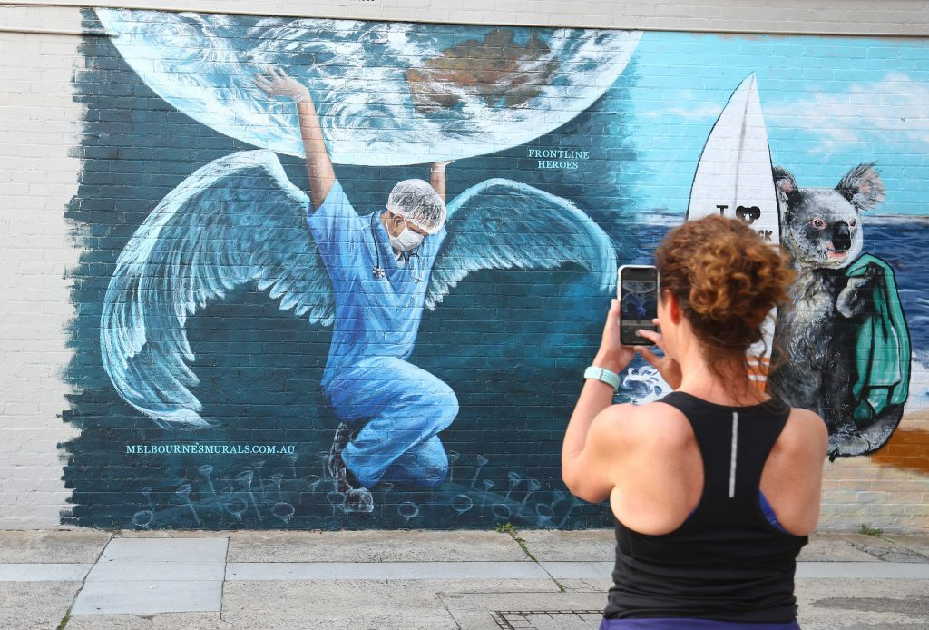 individual taking a photo of street art