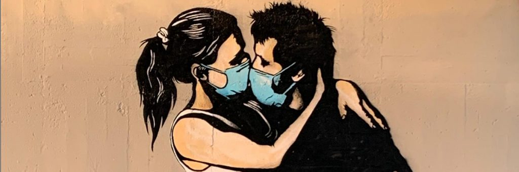 couple kissing while wearing masks